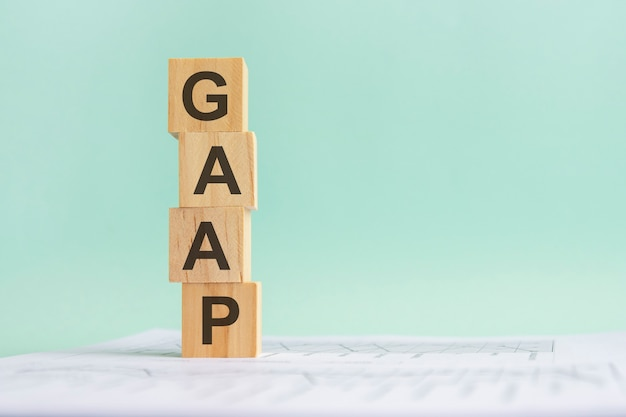 Word gaap com blocos de construção de madeira, fundo azul claro. documento com números no plano de fundo, conceito do negócio. espaço para texto à direita. vista frontal