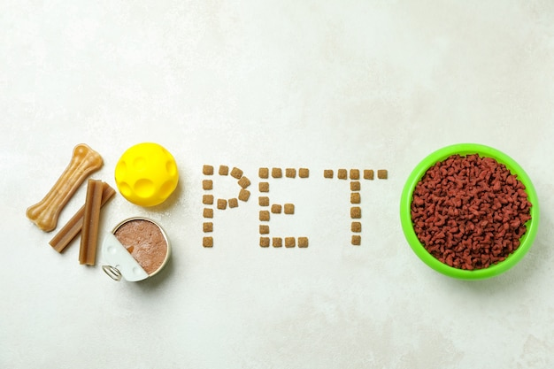 Word pet feito de ração, ração e bola de brinquedo em textura branca