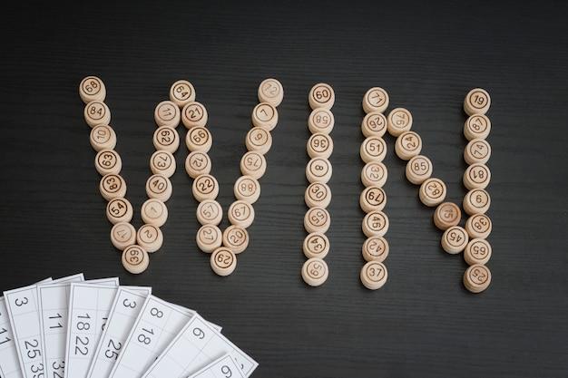 Word win de barris de madeira. mesa de madeira preta. cartões de loteria