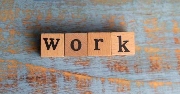 Work palavra escrita em um bloco de madeira colocado em uma placa de madeira, luz desfocada