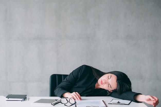 Workaholic multitarefa feminina. retrato de mulher de negócios jovem exausto, dormindo na mesa do escritório.