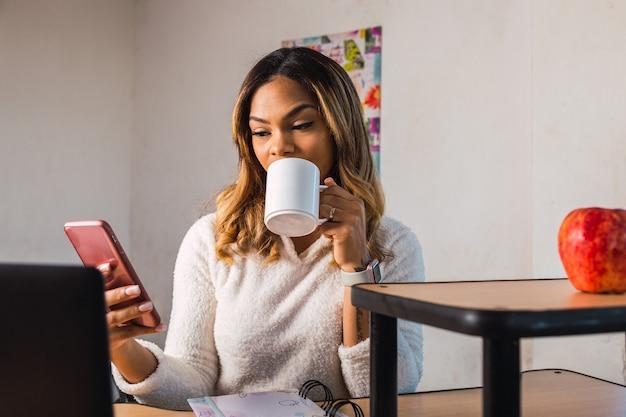 Working at home - mulher latina trabalhando em casa usando seu smartphone e bebendo uma infusão.