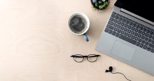 Working business space treinamento de educação on-line microfone de café para laptop em uma mesa de madeira, vista de cima, cópia de banner de espaço