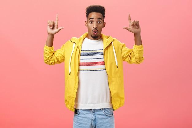 Wow incrível cópia sace look. retrato de um cara de pele escura, bonito e entusiasmado, vestindo uma jaqueta de popelina amarela, dobrando os lábios, levantando e apontando para cima, surpreso e animado sobre o fundo rosa