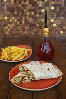 Wrap de frango com pepino e tomate servido com batata frita e coquetel de kiwi