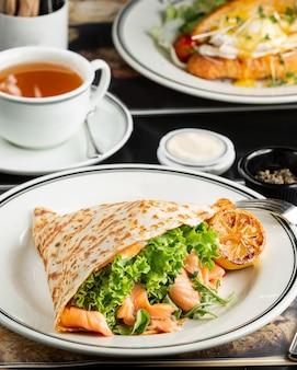 Wrap de salmão defumado com alface e rúcula, servido com limão grelhado