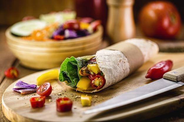 Wrap de tortilha vegana, rolo vegetariano com vegetais grelhados, pimenta, lentilha, tomate e repolho, em uma superfície de madeira rústica
