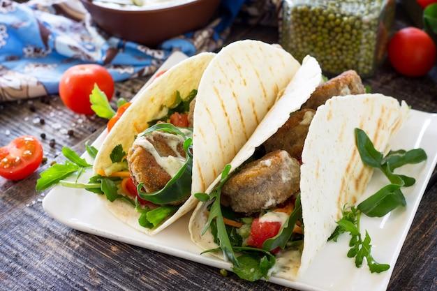 Wrap de tortilla caseira fresca deliciosa com falafel e salada fresca na mesa