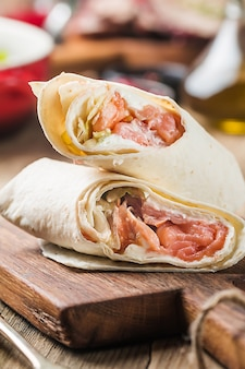 Wrap de tortilla fresca com legumes e salmão em uma tábua de madeira