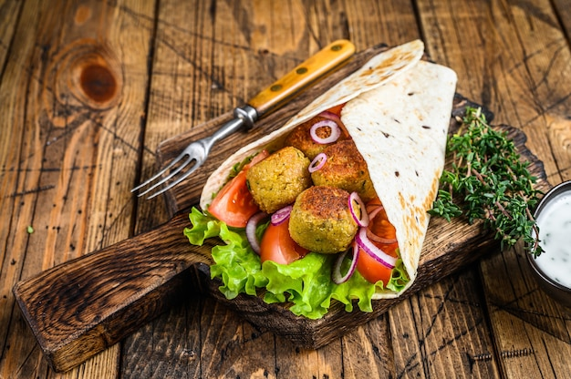 Wrap de tortilla vegetariana com falafel e salada fresca, tacos veganos. fundo de madeira. vista do topo.