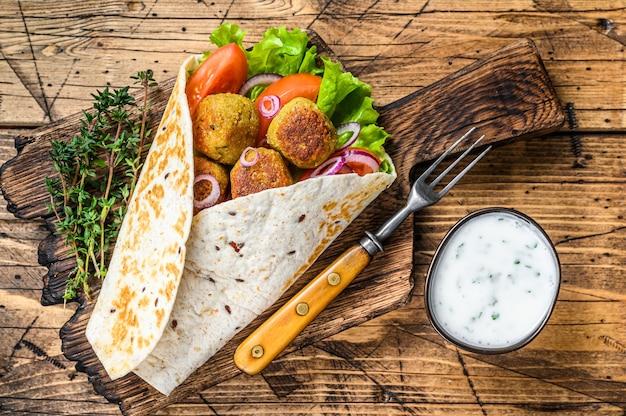 Wrap de tortilla vegetariana com falafel e salada fresca, tacos veganos.