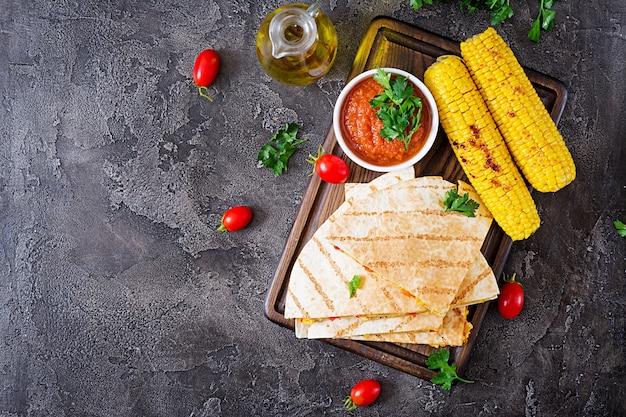 Wrap quesadilla mexicano com frango, milho e pimentão e molho de tomate. vista do topo. configuração plana