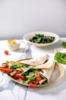 Wrap tradicional de tortila mexicana com carne de porco e legumes em prato de cerâmica servido com pimentões verdes grelhados jalapenos e milho sobre mesa de mármore branco. fast food caseiro