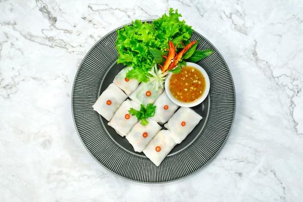 Wraps de arroz com vegetais frescos (kauy tiaw lui suan) ingrediente vegetais e carne de porco picada aperitivo thaifood estilo servido molho de pimenta quente e picante vista superior