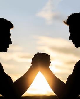 Wrestling de braço de dois homens comparação entre rivalidade e força do desafio pôr do sol, nascer do sol silhueta