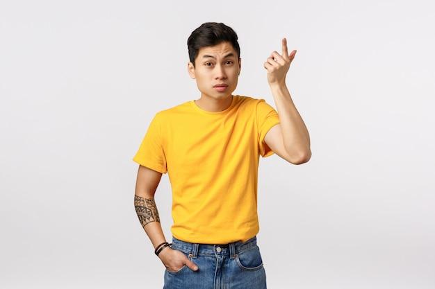 Wtf acontecendo. jovem asiático irritado em camiseta amarela, com tatuagens, levantando o dedo indicador com consternação e irritação, levantando as sobrancelhas como ouvindo bobagem, conversa estranha, parede branca