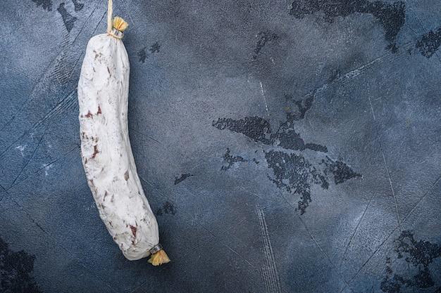 Wurst salchichon espanhol inteiro na superfície azul, vista superior com espaço de cópia.
