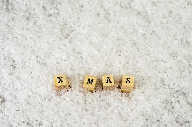 X mas palavra feita de letras em cubos de madeira na neve