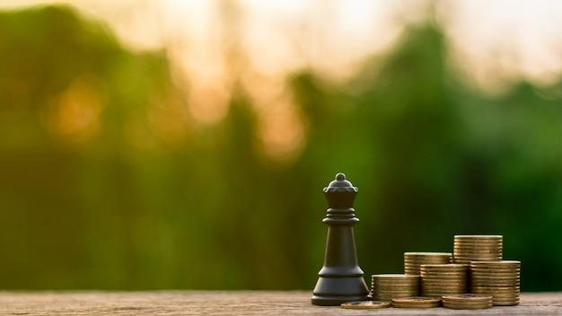 Xadrez da rainha e moedas douradas de uma pilha. - luta e conceito de negócio vencedor.