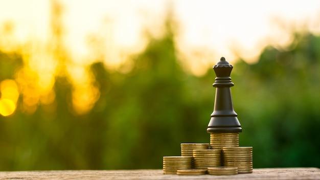 Xadrez da rainha em moedas de uma pilha dourada. - luta e conceito de negócio vencedor.