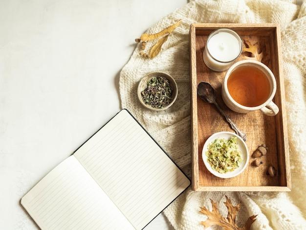 Xadrez de malha, xícara de chá de ervas e bloco de notas aberto