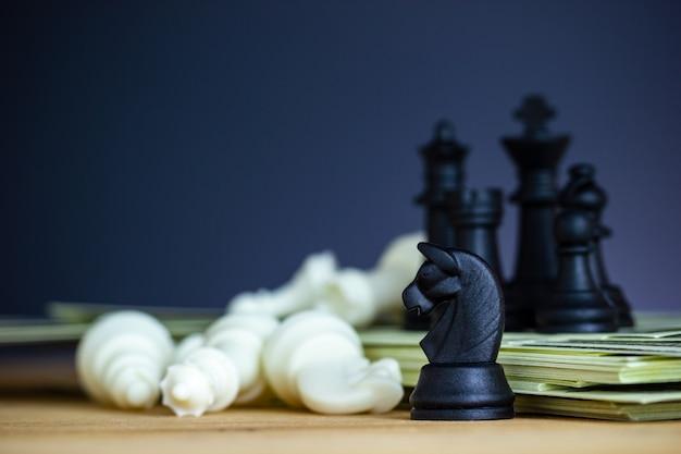 Xadrez preto fica em cima de notas de dólar e mesas de madeira.