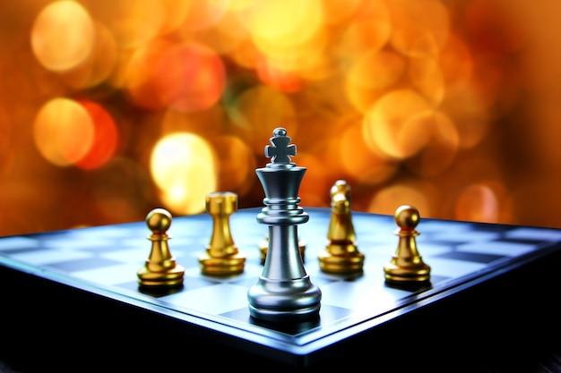 Xadrez rei prateado no tabuleiro de xadrez com fundo abstrato multicolor bokeh padrão