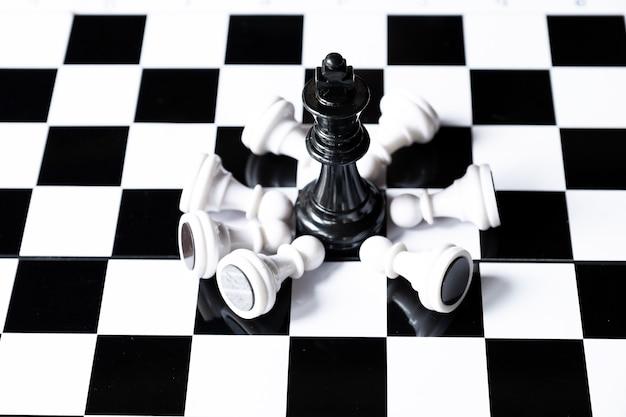 Xadrez rei preto a bordo com exército de xadrez branco desafios do líder planejando a estratégia de negócios