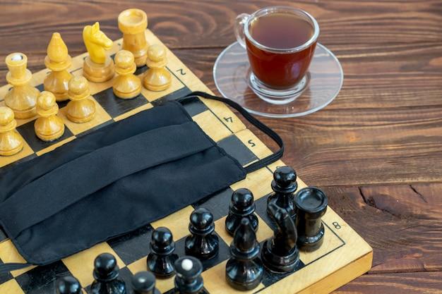 Xadrez velha artesanal em uma placa de madeira. ocupação em férias e quarentena. o conceito de isolamento.