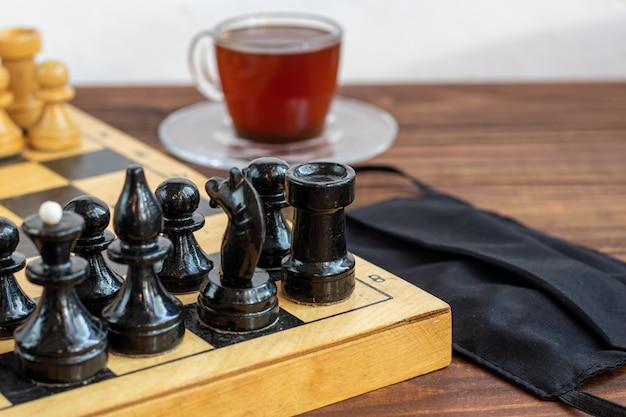 Xadrez velha artesanal em uma placa de madeira. ocupação em férias e quarentena. perto há uma xícara de café e uma máscara médica. o conceito de isolamento.