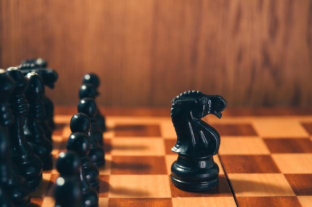Xadrez velho - cavaleiro preto que está à frente das peças de xadrez pretas. conceito de líder.