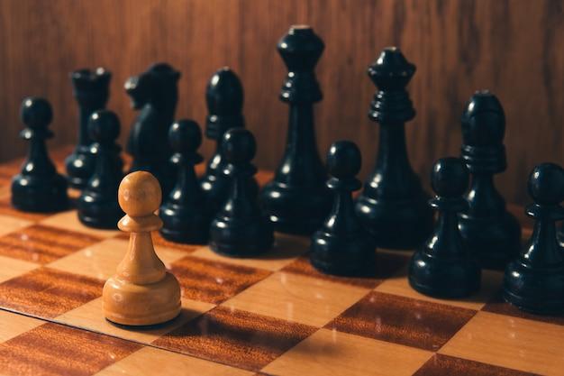 Xadrez velho - peão pequeno que está na frente do jogo de peças de xadrez preto.