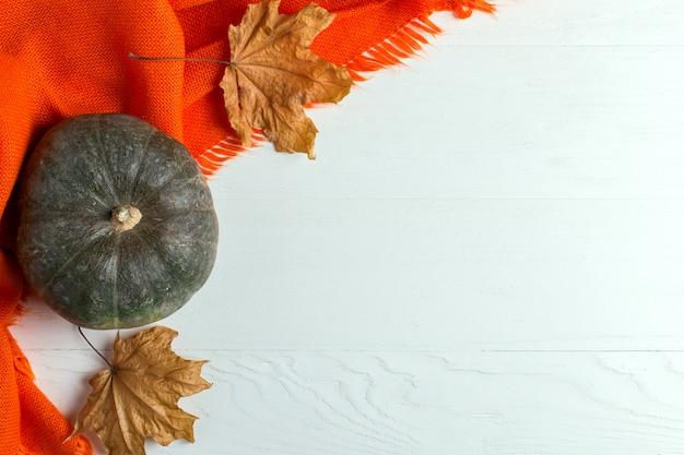 Xaile morno alaranjado brilhante, abóboras e folhas amarelas secas em um fundo branco, humor do outono, copyspace.