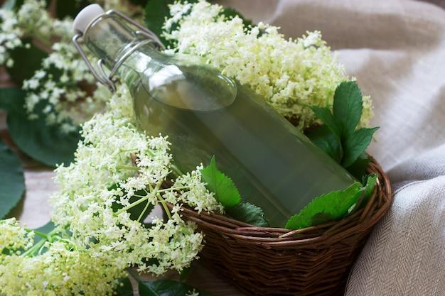Xarope caseiro de flores de sabugueiro em uma jarra de vidro e ramos mais velhos em uma mesa de madeira estilo rústico.