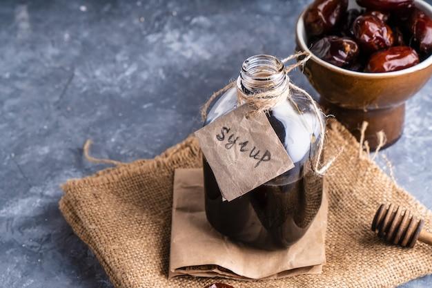 Xarope de datas caseiro em frasco de vidro na mesa de pedra cinza.