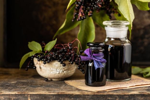 Xarope de sabugueiro preto fresco em uma garrafa de vidro sobre uma mesa de madeira. copie o espaço