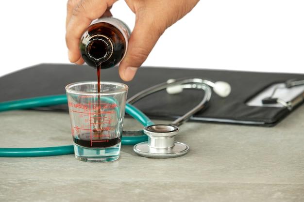 Xarope médica fluindo de uma garrafa em uma colher nas mãos