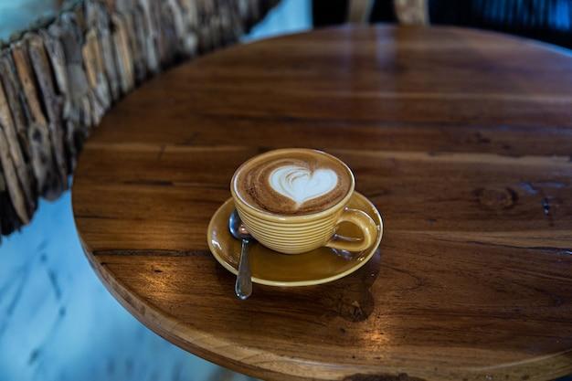 Xícara amarela na moda de cappuccino quente no fundo da mesa de madeira.