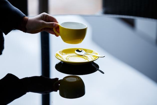 Xícara amarela para café ou chá com um pires nas mãos de uma garota no fundo de uma mesa de vidro.