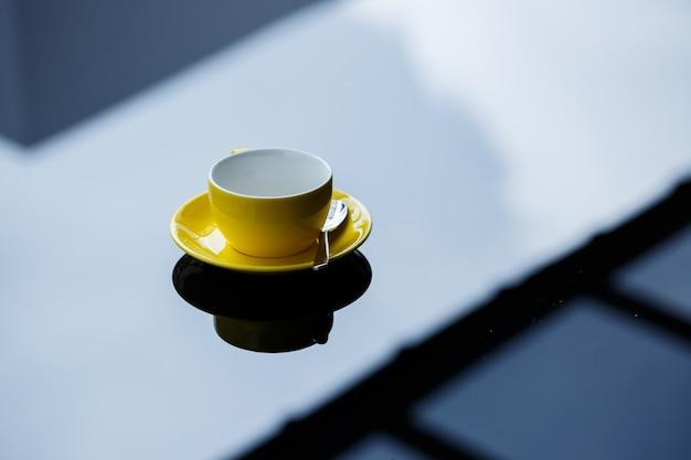 Xícara amarela para café ou chá com um pires sobre uma mesa de vidro.