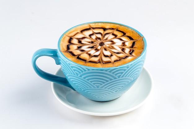 Xícara azul isolada de café fresco com latte art