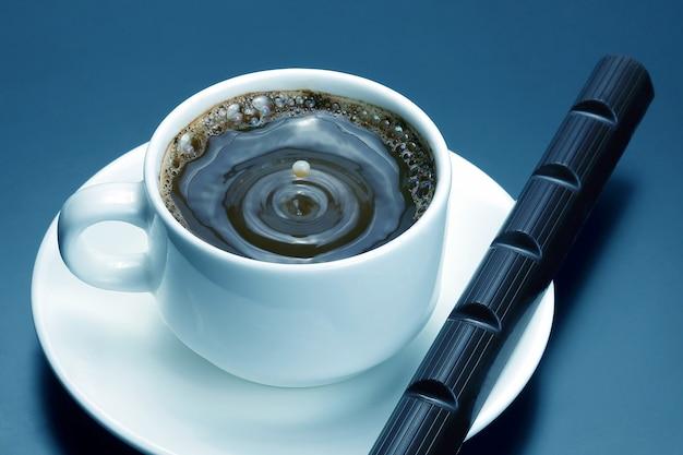 Xícara branca com café preto e chocolate no pires. bebida quente