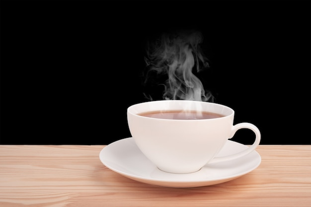 Xícara branca com chá quente na mesa de madeira isolada no fundo preto. vista lateral. xícara chinesa de porcelana branca de chá preto e pires