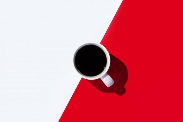 Xícara branca com um café em um espaço branco e vermelho. vista superior, configuração plana. padronizar