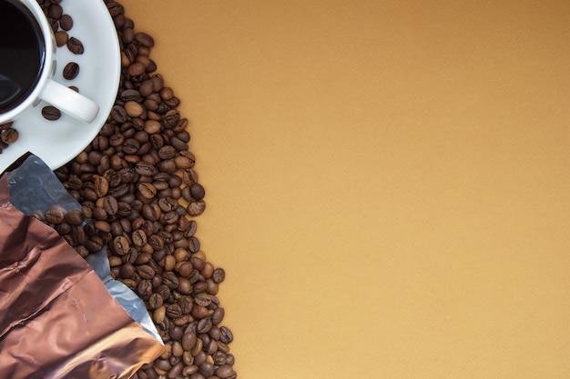 Xícara branca de café americano preto sem leite com um punhado de grãos de café torrados espalhados da embalagem de papel. fundo do café, vista superior com espaço de cópia para logotipo ou texto.