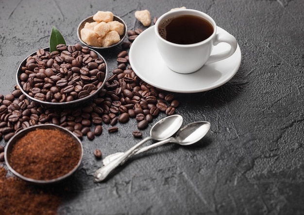 Xícara branca de café orgânico cru fresco com feijão e pó moído com cubos de açúcar de cana com folha de cafeeiro em fundo escuro.