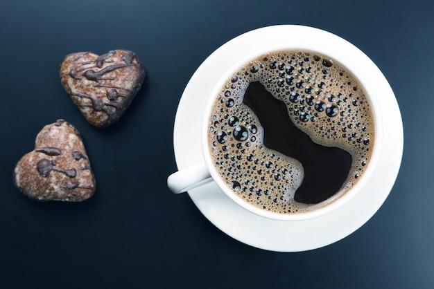 Xícara branca de café preto com biscoitos no escuro