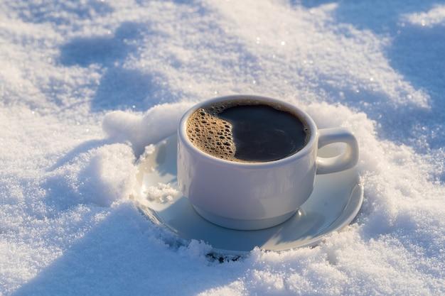 Xícara branca de café quente em uma cama de neve e fundo branco, close-up. conceito de manhã de inverno natal