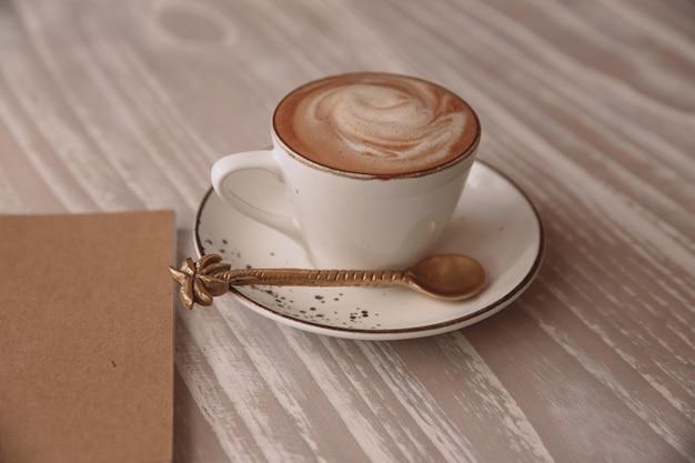 Xícara branca de cappuccino quente em fundo de mesa de luz de madeira.