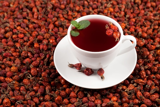 Xícara branca de chá de ervas de hibisco e frutas secas de rosa mosqueta.